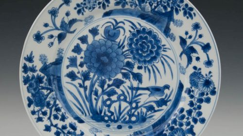 A blue white porcelain plate – flowers growing out of rocks with a bird – China – 18th century (Kangxi period).